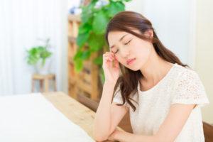頭痛でこめかみを押さえる女性