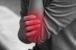 肘の痛みに苦しむ女性