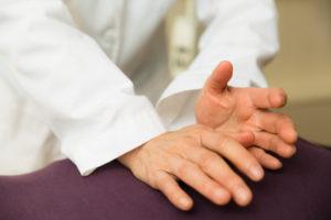 徒手医学で腰痛治療をする男性
